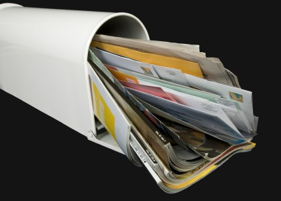 photo of a mail box with junk mail overflowing
