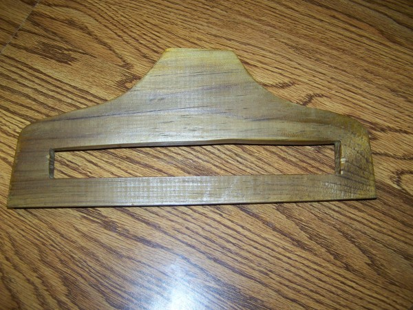 Slotted hanger lying on wood surface