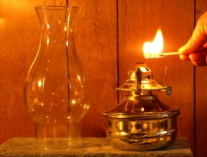 Photo of someone lighting an oil lamp