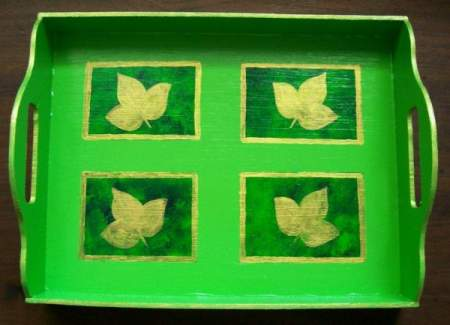 A green decorative tray painted with gold leaves.