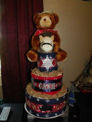 A cowboy themed diaper cake for a baby shower, in red and blue.