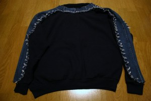 A sweatshirt embellished with jean material on the arms and shoulders.