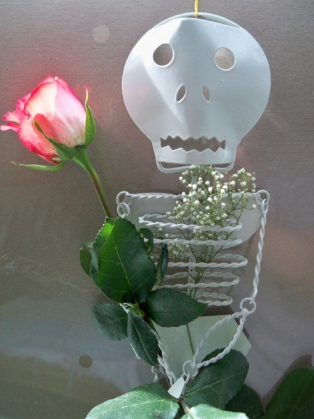 A metal skeleton sculpture with a rosebud.