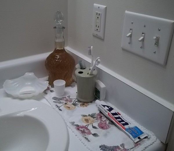 Mouthwash stored in a decorative bottle in the bathroom.