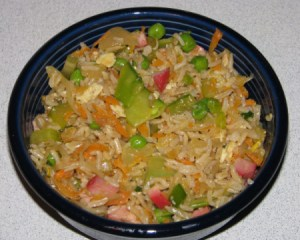 A bowl of homemade fried rice with pork and veggies.