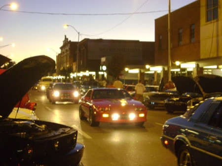 A classic car show with headlights on, at dusk.