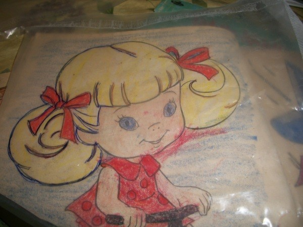 A little girl picture in a coloring book being traced on recycled liners from cereal boxes.