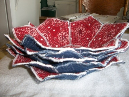 A stack of fabric flower bowls in blue and red.