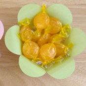 Pastel colored paper flower shaped bowl with candy