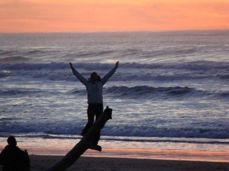 A sunset with a woman with outstretched hands.