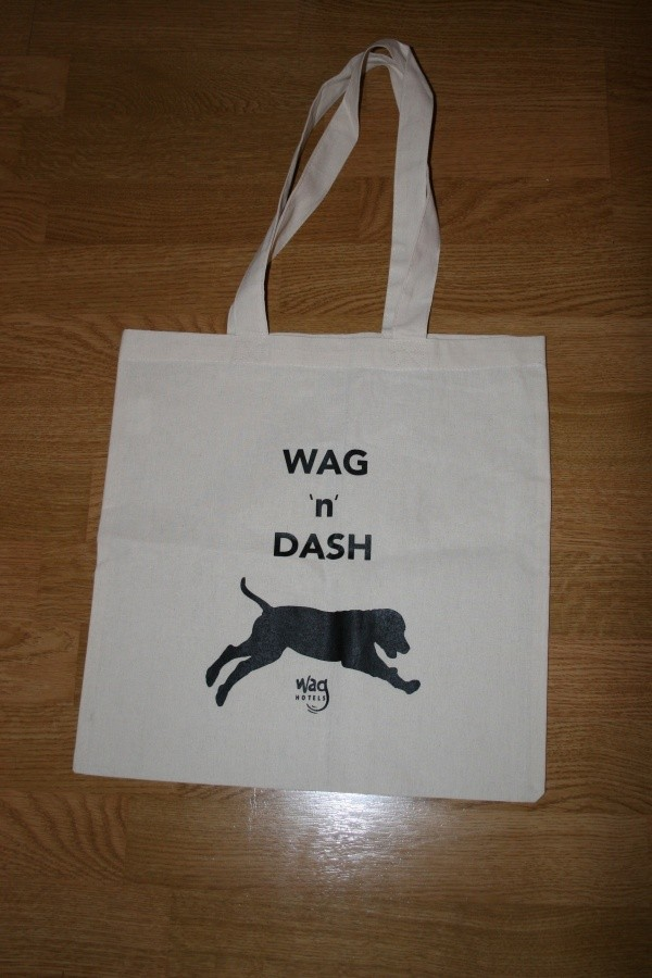 "A white canvas bag that says ""Wag 'n Dash"" in blue"