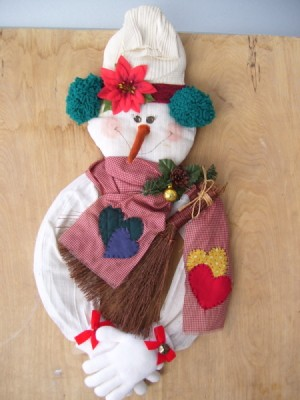 snowman door wreath wearing sweater, knit cap, gloves, and scarf