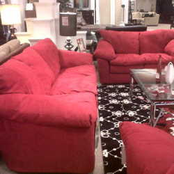 Red couch, loveseat and coffee table arrangement in furniture store