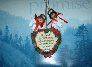 A heart shaped Christmas ornament hanging with two noodle angels over a calendar that says
