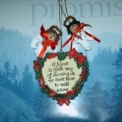 "A heart shaped Christmas ornament hanging with two noodle angels over a calendar that says ""Promise""."