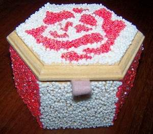 completed pink and white seed bead box with felt loop attached