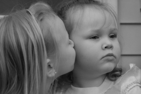 A black and white photo of two young sisters, one kissing the cheek of the other.