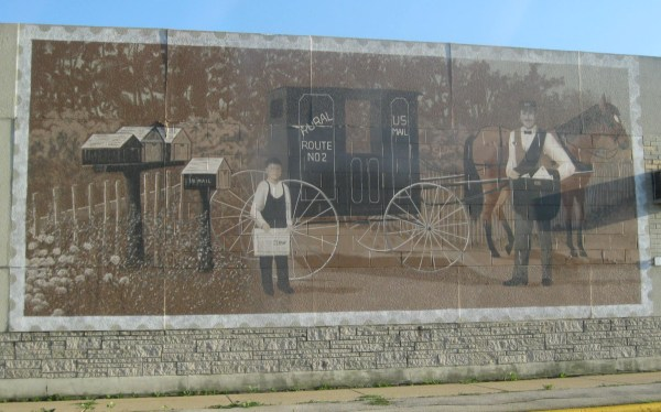 An old fashioned postal scene painted on the side of a post office in Omro, WI.