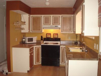 Galley kitchen with white cabinets with brown doors with a white window frame treatment
