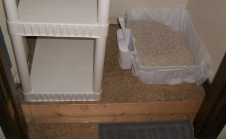 A shelving unit on the floor next to a water heater, with a cat litter pan next to it.