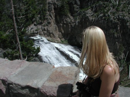 A woman looking out at a waterfall below.