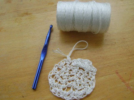 white crocheted pot scrubber, spool of nylon string, and crochet hook