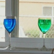 A close up of two wine glasses in a window filled with colored water