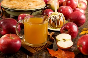 Photo of hot apple cider surrounded by apples.