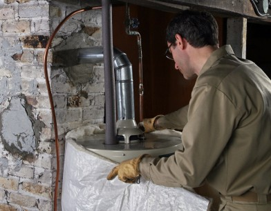 Photo of someone installing a water heater blanket.