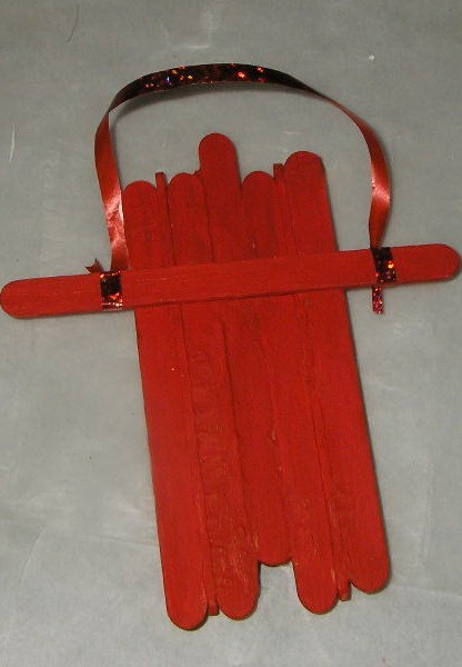 red painted sled with cross member and ribbon pull tied on