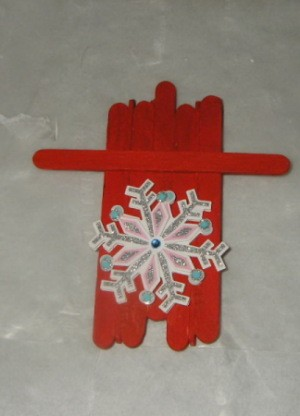 red painted sled with snowflake decoration affixed to top side