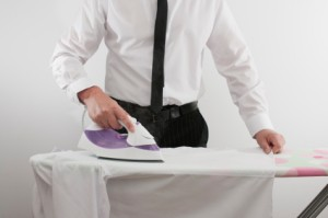 Photo of a man ironing a shirt.