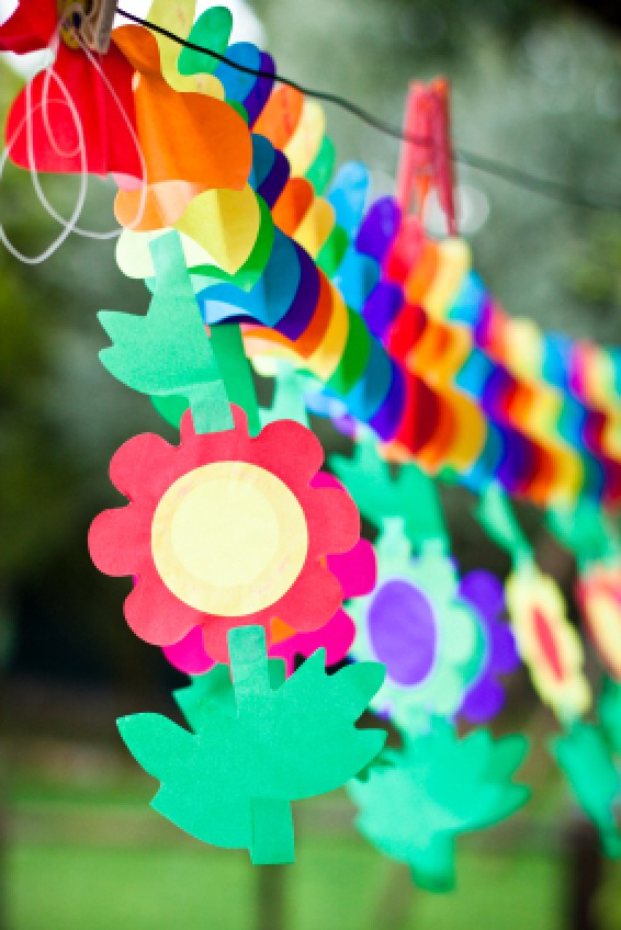 Picture of a colored paper cut into flower shapes and strung together.