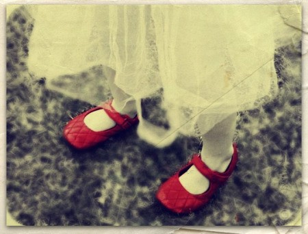 Young girl in tattered skirt and red shoes