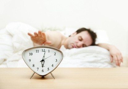 Man in bed hitting snooze button on an alarm clock.