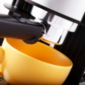 closeup of espresso machine and orange coffee cup