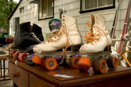 Two pair of roller skates on table at a garage sale.