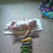 Baby on blanket with veggies placed in front.