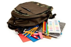 Photo of a back pack, colored pencils, paper and other school supplies.