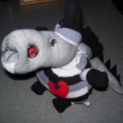 Cute long snouted creature made from a gray, black, and white striped sock. It has a spiky tail and a red bottle cap hanging around its neck.