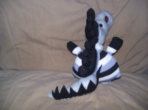 Black, white, and gray creature from the rear. Here the tail is clearly visable.