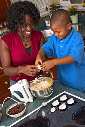 A mother showing her son how to crack an egg.