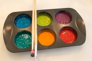 Muffin tin with puffy paint and brushes.