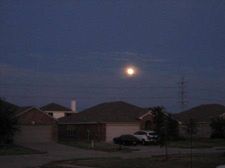 A full moon over a neighborhood.