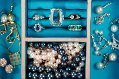 A jewelry box with rings, necklaces and other pieces of jewelry.