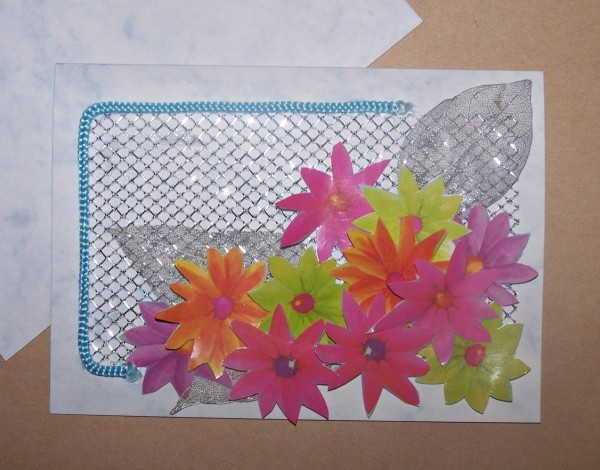 Card embellished with a large cluster of the cut out gift bag flowers. The flowers in various colors adorn the lower right corner of the card. The cord handle is used to complete a partial rectangular shape on the left side and upper left corner.