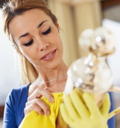 Woman wearing rubber gloves polishing silver.