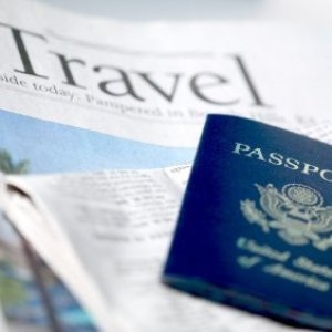 Passport ontop of a travel newspaper page