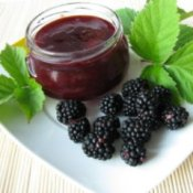 Blackberry Jam Recipes, Jar of blackberry jam on a plate with fresh blackberries.