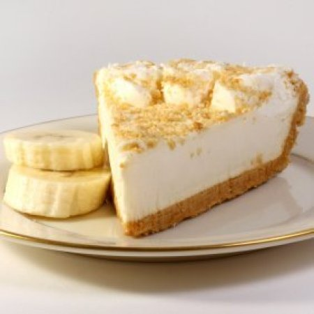 A slice of banana cream pie on a plate with slices of fresh banana.